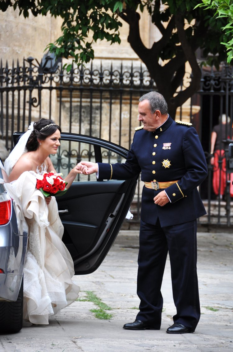 A bride gracefully escorted out of the wedding car by her father.