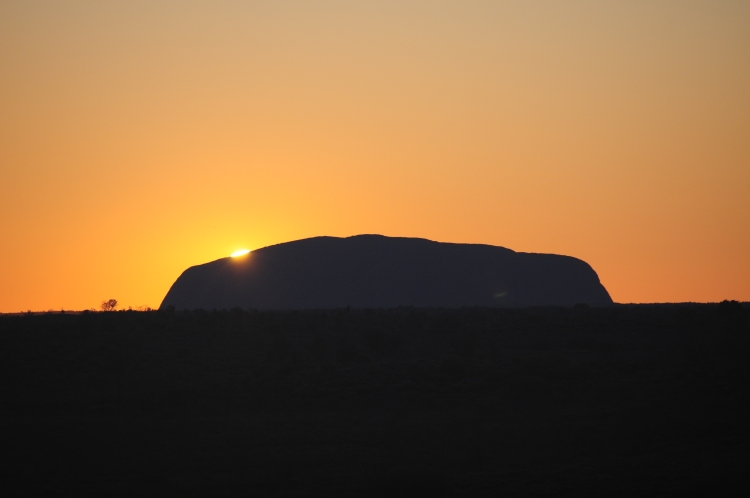 The first peak of the sun rising over Uluru.