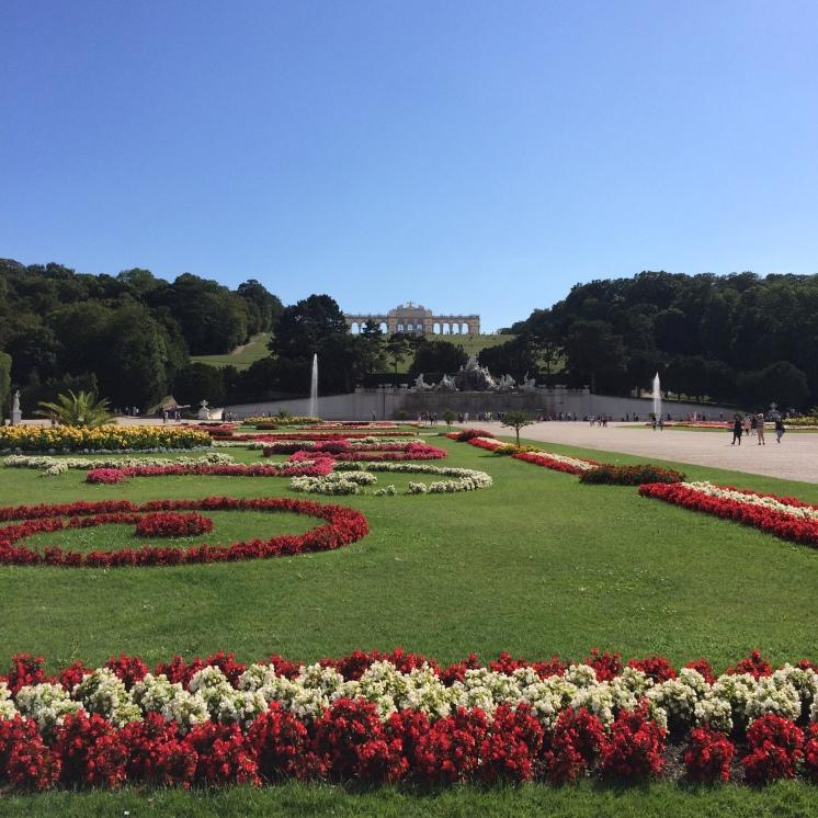 The gardens of Schloss Schonbrunn with the Gloriette on top of the grass hills